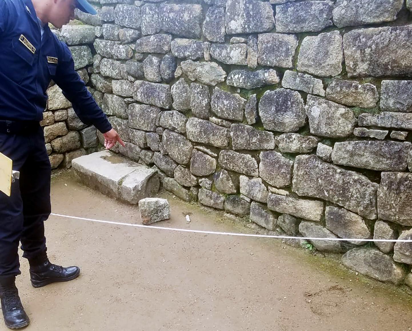 태양의 신전 내에서 떨어진 돌 파편 가리키는 경찰. [AFP=연합뉴스]