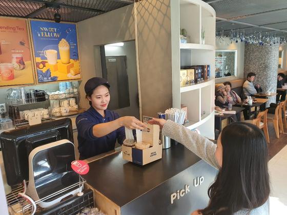 14일 오후 서울 용산구 한남동의 커피 매장을 방문한 손님이 아이스 음료를 구매하고 있다. 추인영 기자