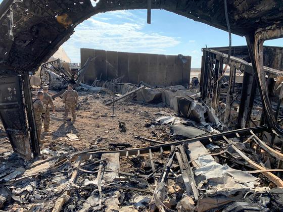 이란 혁명수비대의 미사일 공격으로 무너진 이라크 아인 알아사드 미군 공군 기지가 13일 (현지시간) 언론에 공개 됐다. 현지 주둔 미군들이 폭격을 맞은 현장을 둘러보고 있다. [AP=연합뉴스]