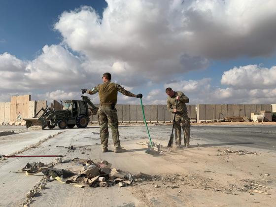 미군들이 13일 (현지시간) 이라크 서부 안바르에 있는 아인 알 아사드 공군기지에서 잔해를 치우고 있다. [AFP=연합뉴스]
