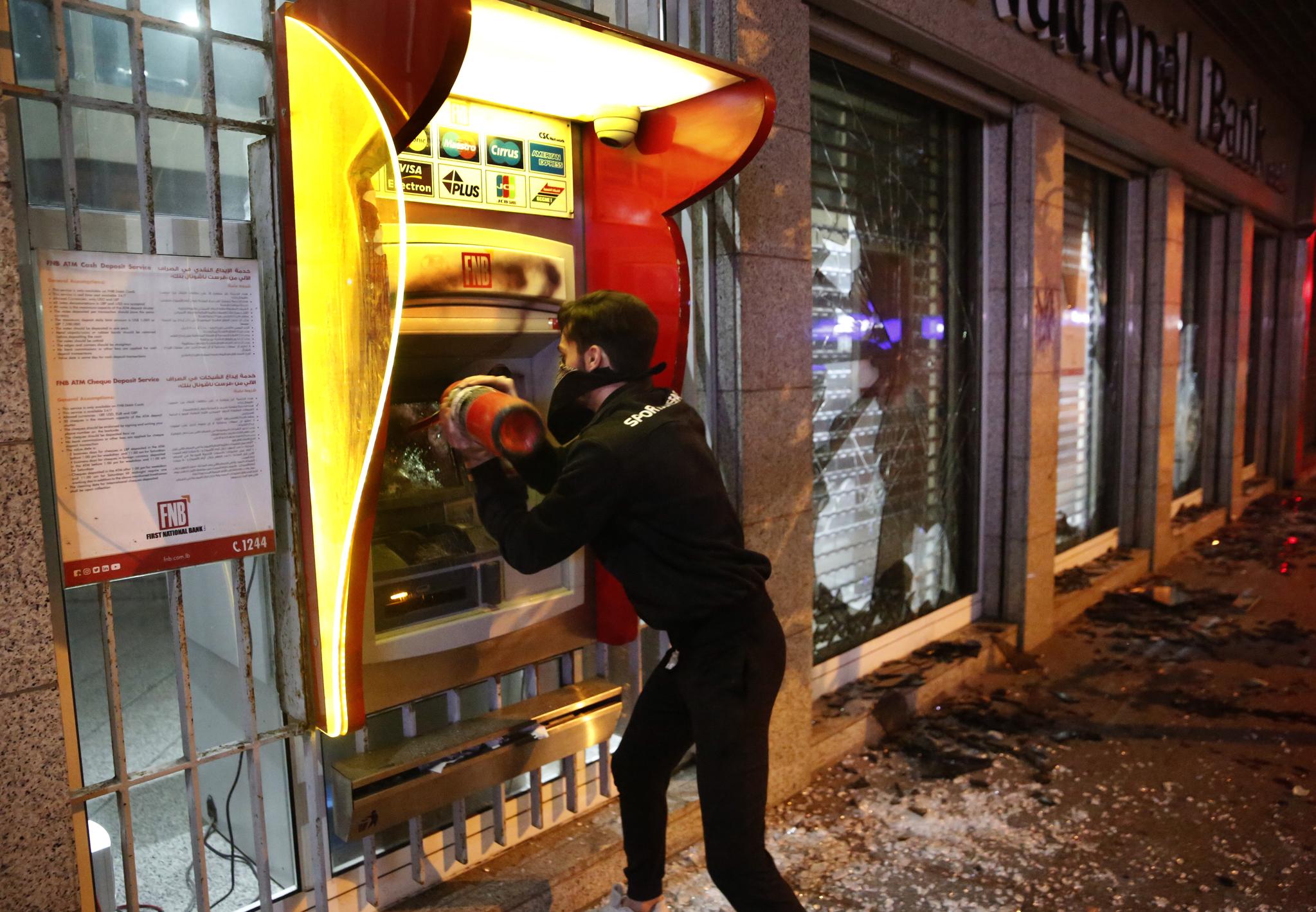 14일(현지시간) 레바논 수도 베이루트의 중심가 하므라 거리에서 한 반정부 시위 남성이 소화기로 현금인출기를 부수고 있다. [AP=연합뉴스]
