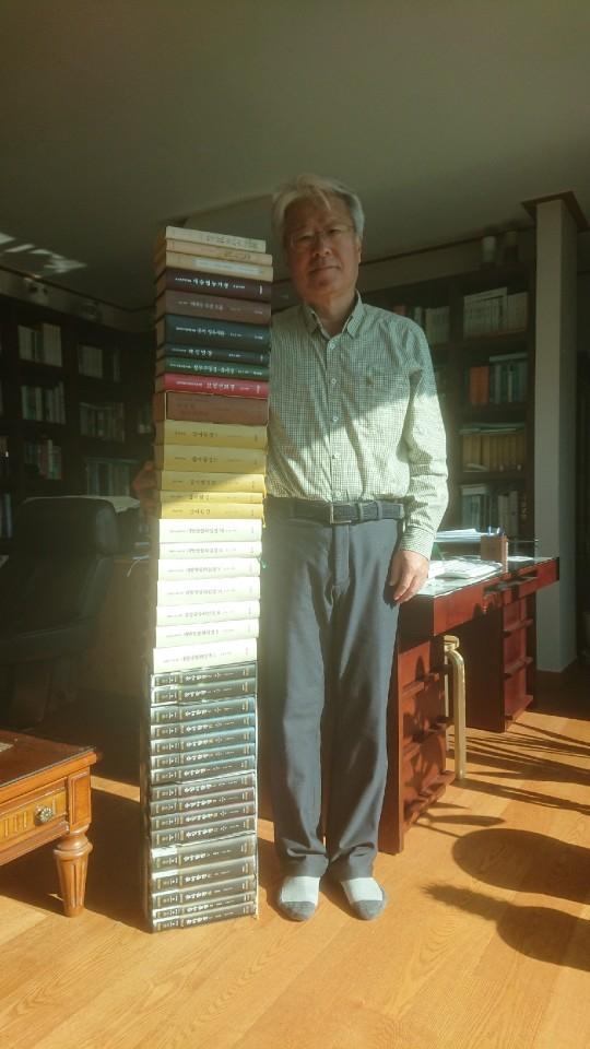 김윤수 전 판사가 지난 15년간 번역한 경전 등 불교 서적은 무려 38권이다. 바닥에서 한 줄로 쌓아올려 보았다. 그의 키만큼 올라왔다. [사진 신동엽]