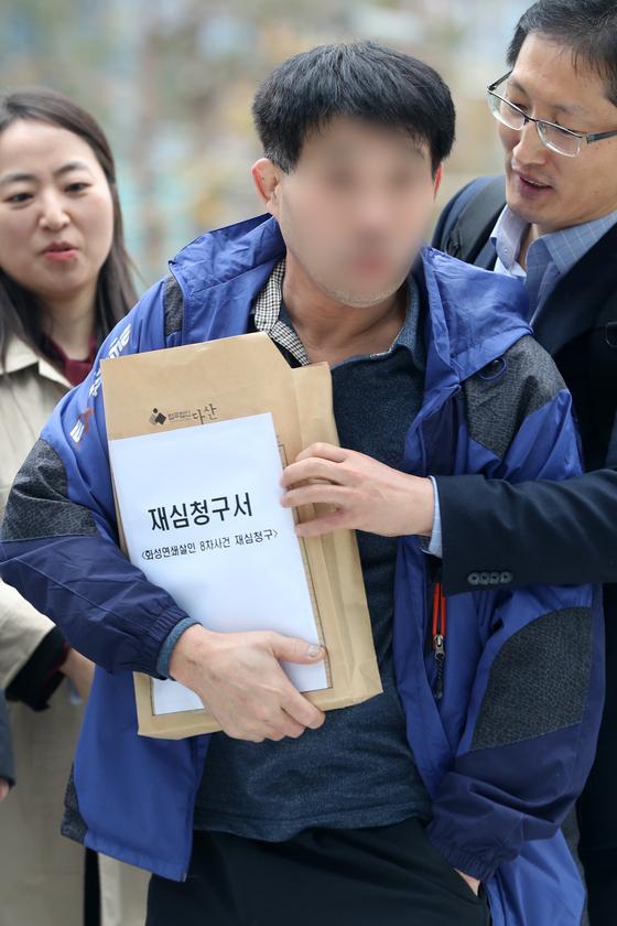 지난해 11월 8차 이춘재 연쇄살인 사건으로 복역 후 출소한 윤모씨(53)와 이주희 변호사, 박준영 변호사가 재심청구서를 제출하기 위해 법원으로 이동하고 있다. [뉴스1]