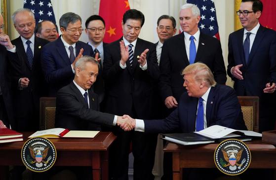 류 허 중국 부총리(왼쪽)과 도널드 트럼프 미국 대통령(오른쪽)이 15일(현지시간) 백악관에서 열린 1단계 무역합의 서명식에서 악수를 나누고 있다. [로이터=연합뉴스]