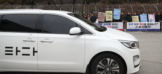 지난 8일 전국택시노동조합연맹과 전국개인택시운송사업조합연합회 등 택시4단체 회원들이 서울 서초구 서울중앙지법 앞에서 '타다' 처벌 촉구 기자회견을 하고 있는 가운데 '타다' 차량이 그 앞을 지나고 있다. [연합뉴스]