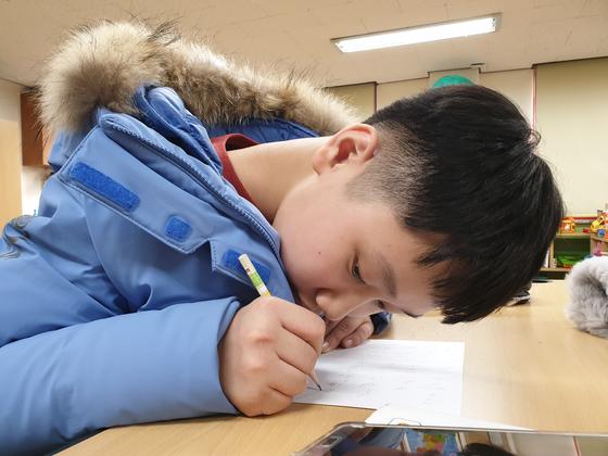 6년전 서울의 한 공공수영장에서 물놀이 사고를 당해 시력을 잃은 정은우(13)군이 한글을 다시 배워 편지를 쓰고 있다. [이소현씨 제공/당사자 동의없이 사진 사용금지]