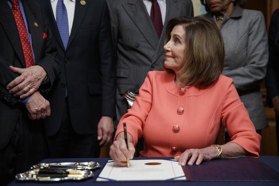 펠로시 의장이 15일(현지시간) 동료의원들에 둘러싸여 상원으로 탄핵 결의를 보내는 서류에 서명하고 있다. [EPA=연합뉴스]