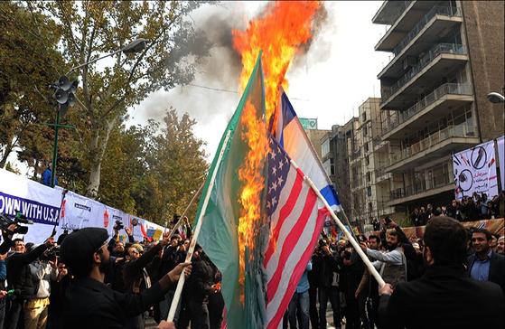 2015년 이란 수도 테헤란 시내에서 시위대가 미국과 이스라엘, 그리고 사우디아라비아의 국기를 불태우고 있다. 국기 훼손은 모욕을 부르고, 모욕은 증오와 원한으로 이어지게 마련이다. [위키피디아]