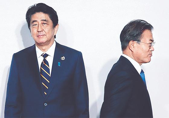 문재인 대통령이 지난해 6월 28일 일본 오사카에서 열린 G20 정상회의 환영식에서 아베 신조 일본 총리(왼쪽)와 악수한 뒤 이동하고 있다. [청와대사진기자단]