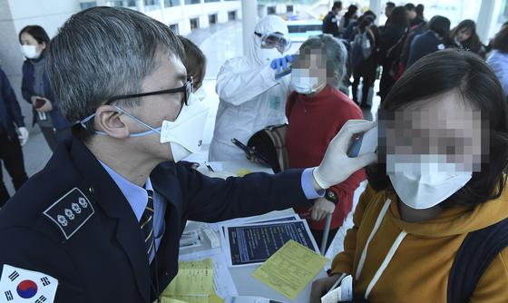 국내에서 중국 '우한 폐렴' 확진자가 발생한 가운데 20일 오후 인천국제공항 제2여객터미널 입국장에서 중국 우한에서 출발해 인천공항에 도착한 승객들을 검역원들이 발열 검사를 하고 있다. [뉴시스]