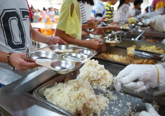 교직원의 점심시간 복무를 두고 교육계 갈등이 커지고 있다. 지난해 7월 서울의 한 초등학교에서 학생들이 점심 급식을 배식받고 있다. 사진은 기사와 직접적인 관련이 없음. [연합뉴스]