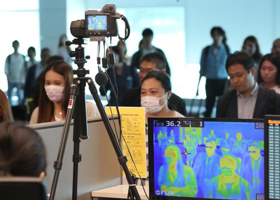 인천국제공항 제2터미널에서 입국객들이 체온을 측정하기 위한 열화상카메라 앞을 지나고 있다.[연합뉴스]