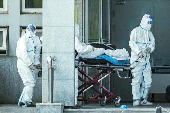 중국에서 신종 코로나 바이러스에 감염된 환자가 계속 늘고 있는 18일(현지시간) 중국 후베이성 우한에 위치한 진인쩌 병원에서 의료진이 폐렴 환자를 이송하고 있다. [AFP=연합뉴스]