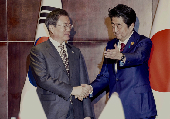 제7차 한·중·일 정상회의 참석을 위해 중국 쓰촨성 청두를 방문 중인 문재인 대통령(왼쪽)이 지난해 12월 24일 오후(현지시간) 아베 신조 일본 총리를 만나 악수하고 있다. [청와대사진기자단]