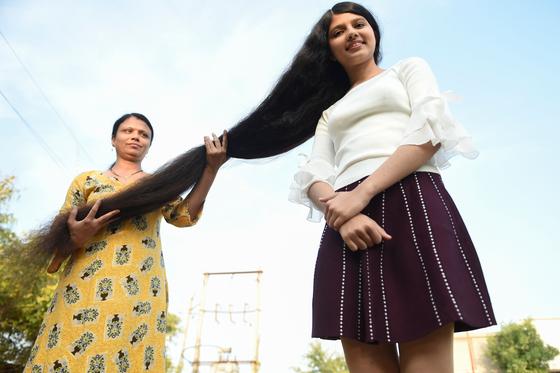 닐란시 파텔의 긴 머리를 그의 어머니가 펼처보이고 있다. [AFP=연합뉴스]