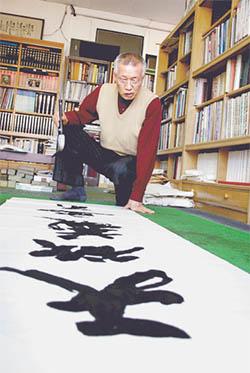 당대 명필로 손꼽힌 학정 이돈흥 선생이 생전 작업실에서 붓글씨를 쓰는 모습. [중앙포토]