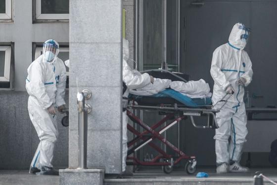 중국에서 신종 코로나 바이러스에 감염된 환자가 계속 늘고 있는 18일(현지시간) 중국 후베이성우한에 위치한 진인쩌 병원에서 의료진이 폐렴 환자를 이송하고 있다. [AFP=연합뉴스]