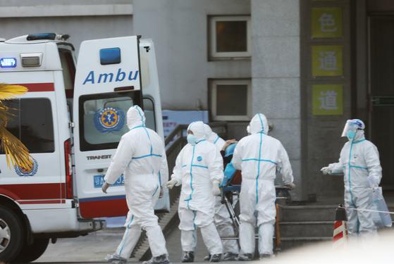 21일(현지시간) 로이터 통신 등은 중국에서 온 30대 여행객이 신종 코로나 바이러스에 감염된 것으로 확인됐다고 CDC를 인용해 보도했다. 사진은 중국 현지에서 이송 중인 신종 코로나 바이러스 환자. [EPA=연합뉴스]