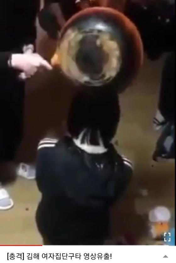 지난 19일 오전 6시쯤 경남 김해 한 아파트 인근에서 10대 여학생이 무릎 꿇은 후배 머리 위에 소주를 붓고 뺨을 때리는 모습. [사진 유튜브 캡처]