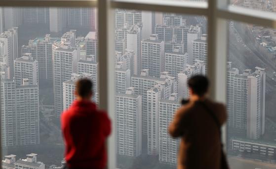 서울 잠실 롯데월드타워를 찾은 시민들이 인근 아파트 단지를 보고 있다. [연합뉴스]