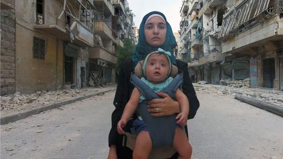 시리아 내전을 기록한 다큐멘터리 '사마에게'의 포스터 사진. .파괴된 동알레포의 모습을 배경으로 전쟁터에서 낳아 기른 딸 사마를 와드 알카텝 감독이 안고 있다. [사진 엣나인 필름 제공]