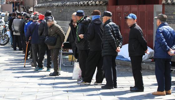 서울 종로구 탑골공원 인근에서 어르신들이 무료 급식을 받기위해 줄지어 서있다.[연합뉴스]