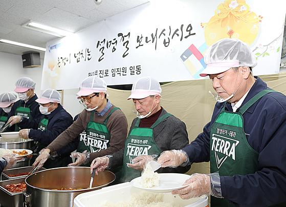 김인규 하이트진로 사장(오른쪽에서 첫번째)과 임직원들이 23일 서울역 인근 무료급식소 따스한 채움터에서 노숙인들에게 배식 나눔봉사 활동을 하고 있다. 하이트진로 제공