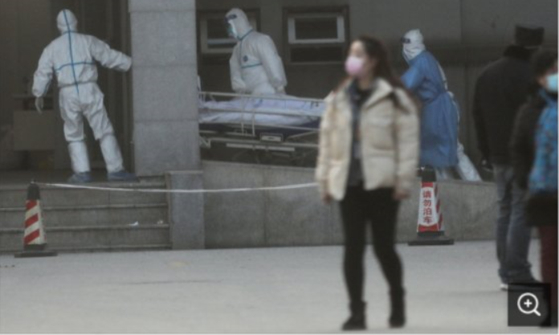 중국 의료진이 지난 20일(현지시간) 중국 우한에서 신종 코로나바이러스 감염환자를 병원으로 이송하고 있다. [로이터=연합뉴스]