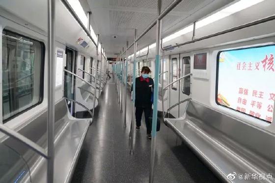 중국 우한시 당국이 23일 운행을 전면 중단시킨 지하철에서 한 직원이 텅 빈 객차 안을 마스크를 쓴 채 정리하고 있다. [사진 웨이보 캡처]