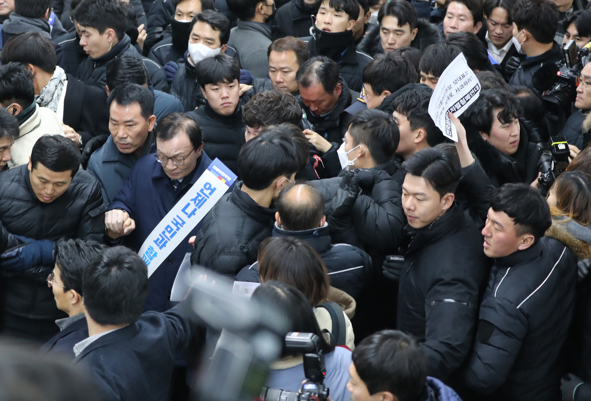 더불어민주당 이해찬 대표가 23일 오전 서울 용산역에서 귀성객들에게 설 인사를 한뒤 장애인 단체의 사과 요구를 받으며 승강장을 빠져나가고 있다. [연합뉴스]