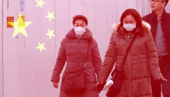 22일 오후 서울 명동거리를 찾은 관광객들이 마스크를 쓴 채 관광을 하고 있다. [뉴스1]
