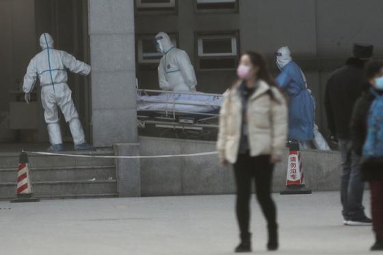 신종 폐렴 환자를 격리 치료하는 중국 우한의 진인탄 병원에서 방역복을 입은 의료진이 환자를 병원으로 옮기고 있다. [로이터=연합뉴스]