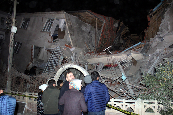 24일(현지시간) 규모 6.8의 지진이 발생한 터키 동부 엘라지 지역의 무너진 건물 주변에 주민들이 모여 있다. [EPA=연합뉴스]