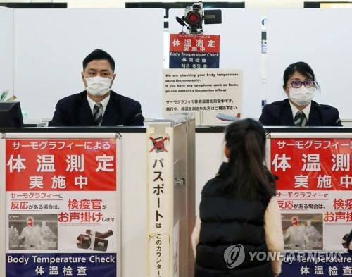 우한 폐렴에 대한 우려가 커진 가운데 일본 나리타 공항에서 당국자들이 여행자들의 체온을 확인하고 있다. [EPA=연합뉴스]