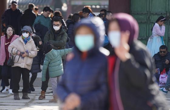 설 연휴 사흘째이자 국내에서 세 번째 우한 폐렴 확진 환자가 발생한 26일 서울 경복궁을 찾은 관람객들이 마스크를 쓰고 궁중을 둘러보고 있다.[연합뉴스]