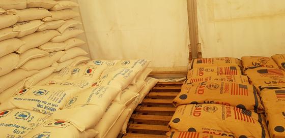 우간다 서부 스웨웨의 유엔세계식량기구(WFP)의 창고에 한국산 쌀이 미국산 옥수수와 나란히 보관되고 있다. 원조 받던 한국이 원조하는 국가로 바뀌었음을 상징적으로 보여주는 장면이다. WFP는 한국 정부가 우간다 등에 지원하는 쌀의 guswkd 분배를 위탁 받았다. [채인택 기자]