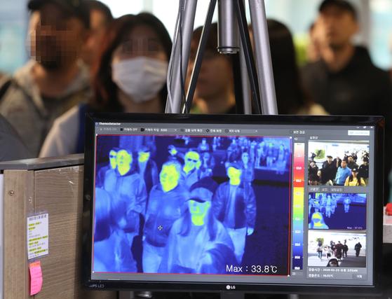 지난 23일 오후 인천국제공항 1터미널 입국장에서 질병관리본부 국립검역소 직원들이 열화상 카메라로 승객들의 체온을 측정하고 있다.  [연합뉴스]