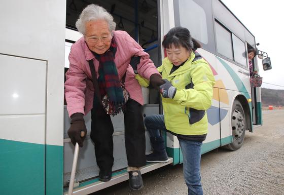 22일 경남 합천군 삼가면 한 마을 앞에서 버스도우미 김영애(50·여)씨가 어르신의 하차를 돕고 있다. 송봉근 기자
