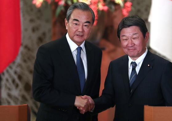왕이(왼쪽) 중국 국무위원 겸 외교부장이 지난해 11월 일본을 방문해 모테기 도시미쓰 일본 외무상과 악수하고 있다. 모테기 외무상은 26일 왕 부장에게 전화해 신종 폐렴과 싸우고 있는 중국에 대한 지원을 약속했다. [AP=연합뉴스]