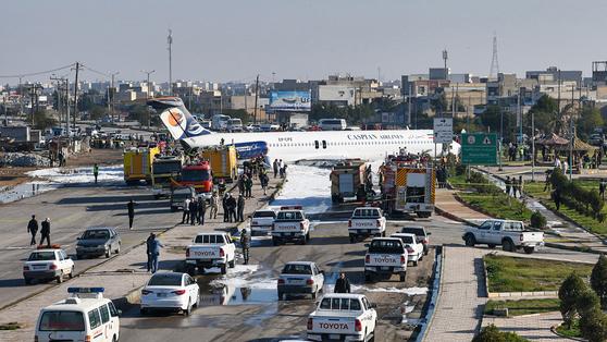 27일(현지시간) 이란 남서부 도시 반다르 마샤르에서 착륙도중 활주로에서 미끄러진 여객기가 공항 외곽 도로까지 튀어나와 멈춰있다. [AFP=연합뉴스]