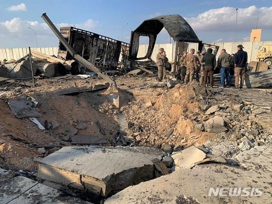 미국 군인들과 기자들이 지난 13일(현지시간) 이라크 아인알아사드 공군기지에 남은 미사일 흔적 옆에 서 있다. 이 기지는 지난 8일 이란의 '거셈 솔레이마니 폭살' 보복공습을 받았다. [AP=뉴시스]