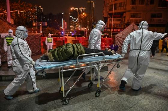 25일(현지시간) 우한폐렴(신종코로나바이러스)dl 처음 발생한 중국 우한시의 적십자사 병원에서 방역복을 입은 의료진들이 감염 추정 환자를 이송하고 있다. [AFP=연합뉴스]