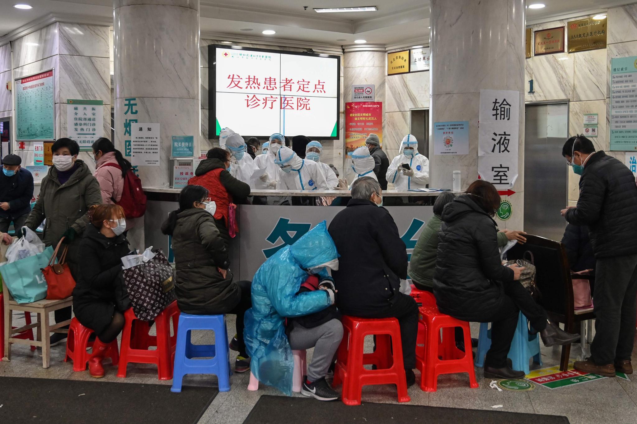 지난 24일 중국 우한의 한 병원에서 사람들이 진료를 기다리고 있다. 뒤로는 보호장구를 착용한 메디컬 스태프의 모습이 보인다. [AFP=연합뉴스]