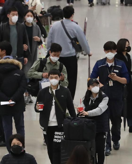 27일 인천국제공항 제1여객터미널에서 마스크를 쓴 관광객들이 입국하고 있다. [뉴스1]