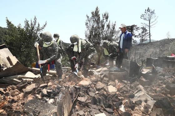 지난 2017년 5월 강원도에서 발생한 산불 현장에 투입돼 잔불을 정리 중인 장병들. [중앙포토]