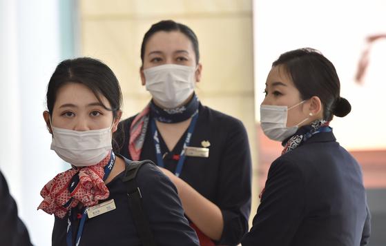 지난 25일(현지시간) 호주 시드니 공항에서 상하이발 중국동부항공 소속 항공 승무원들이 마스크를 쓰고 도착하고 있다. [AFP=연합뉴스]