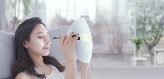 바깥에서 시간을 쪼개 받던 피부관리를 집에서 TV를 보며 매일 할 수 있다는 것이 최근 뷰티 기기 인기 상승의 배경이다. 기업들도 더 다양한 제품을 선보이고 있다. 한 여성 모델이 LG '프라엘 더마' LED 마스크를 사용하고 있다. [사진 LG전자]