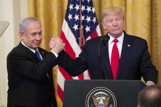 도널드 트럼프 미국 대통령이 28일 백악관 이스트룸에서 팔레스타인 제한적 독립국 수립과 500억 달러 민간 투자를 포함한 자신의 중동 평화안을 발표하며 벤야민 네타야후 이스라엘 총리와 손을 굳게 잡았다.[EPA=연합뉴스]