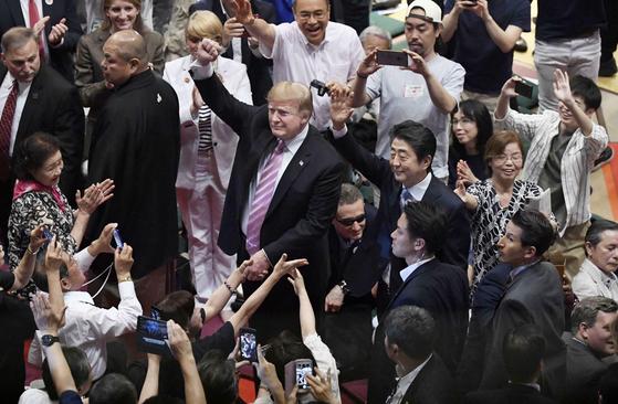 트럼프 미국 대통령과 아베 일본 총리가 지난해 5월 26일 일본에서 스모를 관전하는 동안 관객들이 스마트폰으로 그 장면을 찍고 있다. [교도=연합뉴스]
