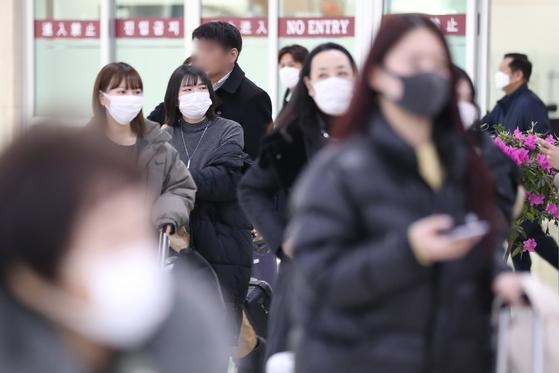 28일 서울 김포공항으로 들어온 중국발 여행기 승객이 마스크를 쓴 채 입국장을 나오고 있다. [연합뉴스]